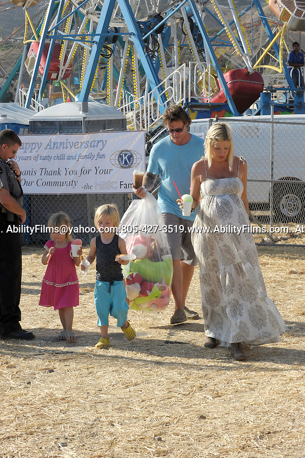 September 4th 2011  ..Tori Spelling walking with kids & her husband Dean McDermott at the Malibu Chili Cookoff carnival fair. Holding Goldfish which PETA will soon make illegal to give away at fairs Dean was holding a huge plastic bag filled with pink stuffed animals. Tori took some pictures of all the paparazzi while holding her snow cone. Tori bent over to show off her big butt while the kids finished eating up there hotdogs... AbilityFilms@yahoo.com.805-427-3519.www.AbilityFilms.com..