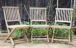 Three wooden garden chairs next to each other