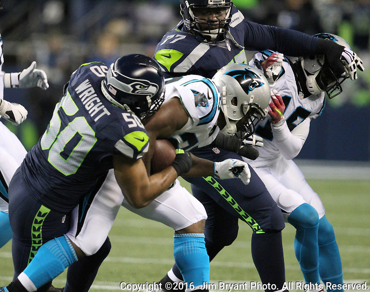 Seattle Seahawks outside linebacker K.J. Wright (50) and Seattle Seahawks defensive tackle Ahtyba Rubin (77) team up to bring down Carolina Panthers running back Jonathan Stewart (28) at CenturyLink Field in Seattle, Washington on December 4, 2016.  Wright ripped out the ball on the play. Seahawks beat the Panthers 40-7.  ©2016. Jim Bryant photo. All Rights Reserved.