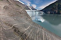 Layered sediments revealed in rock ground smooth by glacier weight and travel. Tidewater face of Cascade glacier and icebergs floating in Barry Arm, Chugach National Forest, Prince William Sound, southcentral, Alaska.