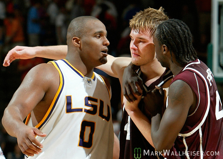 Louisiana State University Tigers center, Glen Davis (0) consoles Texas A&M Aggies center Antanas Kav aliauskas (C) as he is being assisted off the court by teammate Marlon Pompey (R) after Louisiana State University defeated the Texas A&M Aggies 58-57 in the last 3.9 seconds of the game in second round action of the NCAA basketball tournament in Jacksonville, Florida  March 18, 2006.