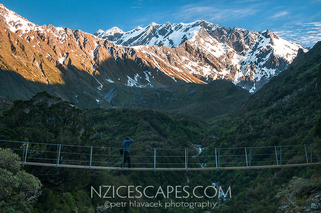 Hiker on swingbridge over Tekano Creek near Douglas Hut in Copland Valley with Southern Alps at sunset in background, Westland Tai Poutini National Park, UNESCO World Heritage Area, West Coast, New Zealand, NZ