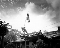 Marine Pvt. 1st Class Luther Leguire raises U.S. Flag at American consulate in Seoul, while fighting for the city raged around the compound.  September 27, 1950.  Sgt. John Babyak, Jr. (Marine Corps)<br /> NARA FILE #:  127-N-A3386<br /> WAR & CONFLICT BOOK #:  1424
