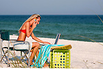 Mobile Vacation Office.  Woman staying connected doing business  on laptop talking on cell phone on beautiful Pensacola Beach.