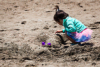 With a tutu and a top knot, an inquisitive youngster takes a closer look at one of the sand scupltures along the beach after the Sand Castle and Sculpture Contest at  Crown Memorial State Beach in Alameda, California.