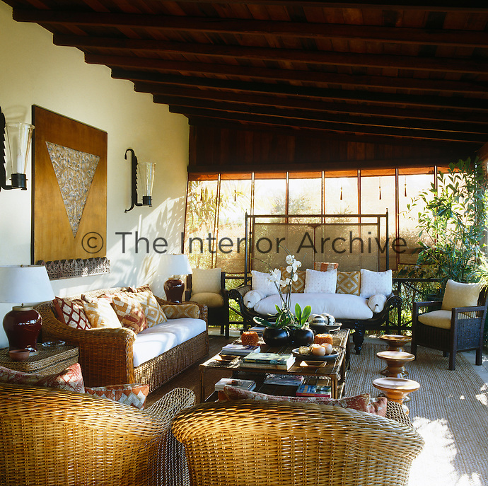One of several terraces is divided into three sitting areas each one furnished with wicker chairs and decorated with bright cushions and textiles