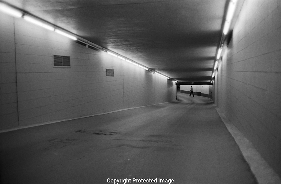 Walking at the end of a tunnel, neaon light illuminated