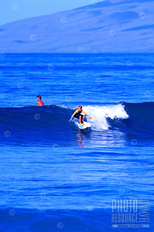 A young boy wearing a wetsuit takes on a small swell at a Maui beach with the west Maui mountains in the background.