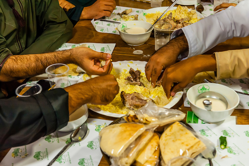 Omani men eating mansaf (the national dish of Jordan), Al-Quds Restaurant, Downtown Amman, Jordan.