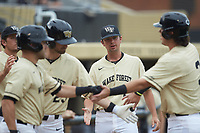 Ben Casstevens (20) of the Wake Forest Demon Deacons congratulates teammate Bobby Seymour (3) during the game against the Miami Hurricanes at David F. Couch Ballpark on May 11, 2019 in  Winston-Salem, North Carolina. The Hurricanes defeated the Demon Deacons 8-4. (Brian Westerholt/Four Seam Images)