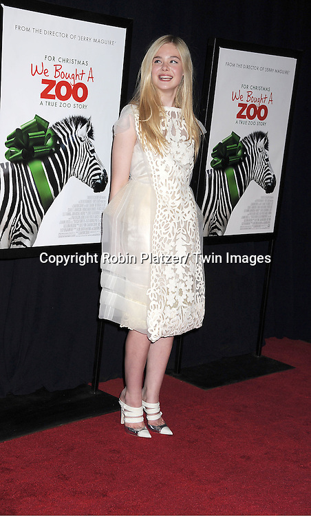 """actress Elle Fanning in Louis Vuitton white cut out dress attends The New York Screening of """"We Bought A Zoo"""" on December 12, 2011 at The Ziegfeld Theatre in New York City. The movie stars Matt Damon, Scarlett Johansson, Thomas Haden Church, Patrick Fugit, Colin Ford, Elle Fanning and John Michael Higgins."""