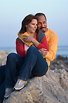 Happy couple at beach, sitting on rock