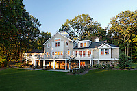 Traditional home exterior at dusk with large deck, cupola, set on expansive lawns.