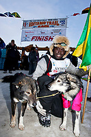 The first ever Jamaican musher, Newton Marshall, poses with his lead dogs at the finish line in Nome during the 2010 Iditarod