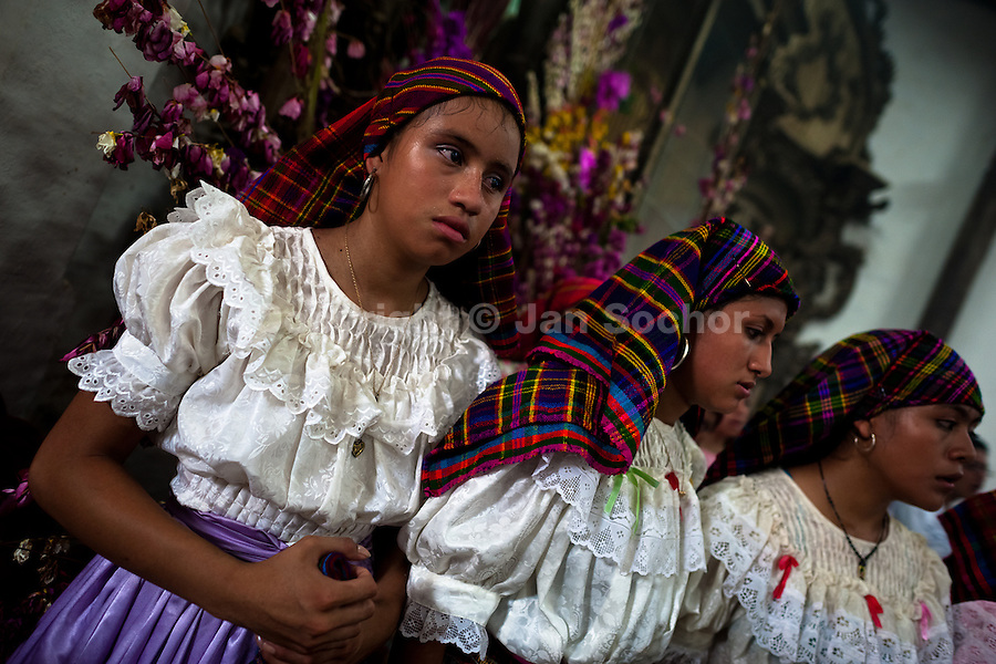 """Salvadoran girls, dressed in typical costumes, pray during the Holy Mass at the end of the Flower & Palm Festival in Panchimalco, El Salvador, 8 May 2011. On the first Sunday of May, the small town of Panchimalco, lying close to San Salvador, celebrates its two patron saints with a spectacular festivity, known as """"Fiesta de las Flores y Palmas"""". The origin of this event comes from pre-Columbian Maya culture and used to commemorate the start of the rainy season. Women strip the palm branches and skewer flower blooms on them to create large colorful decoration. In the afternoon procession, lead by a male dance group performing a religious dance-drama inspired by the Spanish Reconquest, large altars adorned with flowers are slowly carried by women, dressed in typical costumes, through the steep streets of the town."""