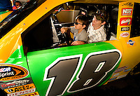 Two boys drive a NASCAR simulator at Food Lion Speed Street in uptown Charlotte, NC.