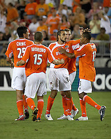 Houston Dynamo midfielder Dwayne De Rosario (14) is congratulated by teammates Brian Ching (25), Alejandro Moreno (15) and Ricardo Clark (13) after scoring on a penalty kick.  Houston Dynamo tied New York Red Bulls 1-1 at Robertson Stadium in Houston, TX on July 29, 2006.