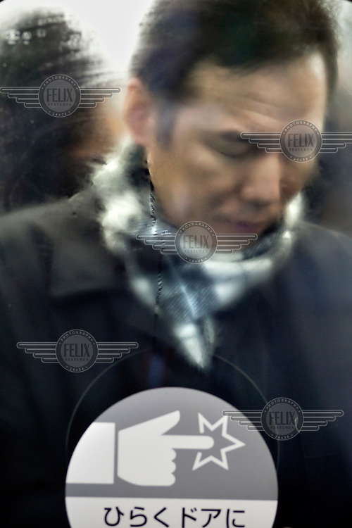 A commuter crammed into one of the train carriages at Shibuya station during morning rush hour.