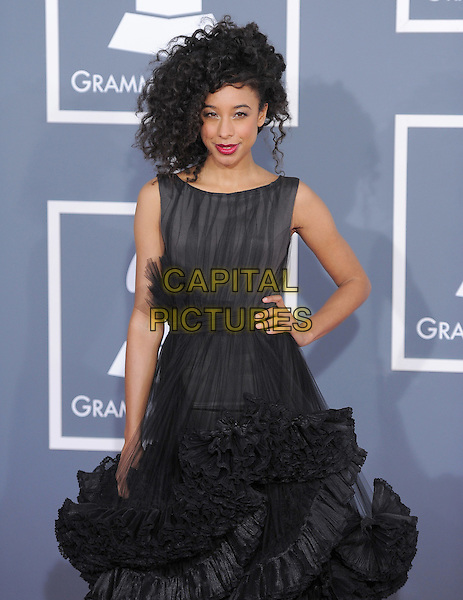 Corinne Bailey Rae.The 54th Annual GRAMMY Awards held at the Staples Center, Los Angeles, California, USA..February 12th, 2012.half length black dress sleeveless sheer hand on hip ruffles ruffled  .CAP/RKE/DVS.©DVS/RockinExposures/Capital Pictures.