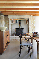 A dolly for hanging damp fabrics hangs infront of the wood burning stove in the rustic kitchen