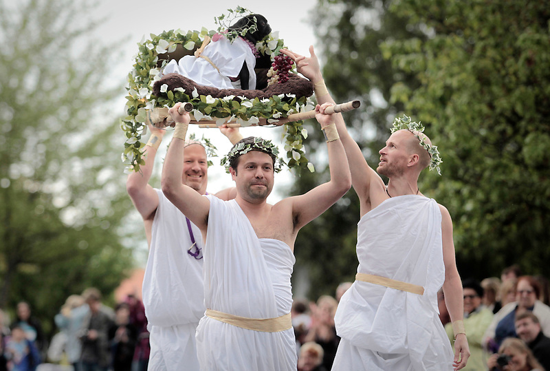 """""""Cleopuglia"""" is seen being carried by men dressed as Egyptian servants in the Parade of Pugs."""