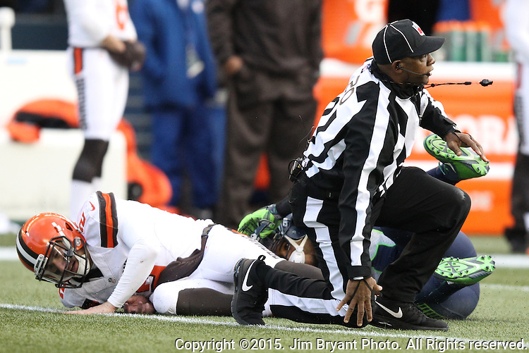 Umpire Barry Anderson (20) gets up off the turf after being hit by Seattle Seahawks linebacker Bobby Wagner (54) and quarterback Johnny Manziel (2)  Cleveland Browns at CenturyLink Field in Seattle, Washington on December 20, 2015. The Seahawks clinched their fourth straight playoff berth in four seasons by beating the Browns 30-13.  ©2015. Jim Bryant Photo. All Rights Reserved.
