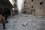 Syrian men walk on the rubble of buildings following a reported bomb barrel attack by Syrian government forces at Salah AL-Dien neighborhood in the northern Syrian city of Aleppo, August 25, 2015. Photo by Ameer al-Halbi