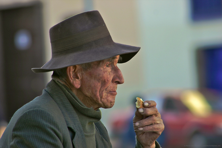 Anciano comiendo pan en las calles de Cuzco.  Pe?rdido en el tiempo y el espacio, la dureza de las manos y el vaci?o de la expresio?n narran la historia de un de los tantos duros trabajadores de la zona.