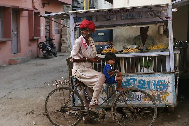 08.10.2008 Dwarka(Gujarat)<br /> <br /> A man and a child on his bike buying sweets.<br /> <br /> Un homme et un enfant sur son velo achetant des g&acirc;teaux.