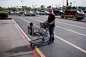 PHOENIX, ARIZONA, USA, 10/2016<br /> Woman and a child in a shopping trolley standing on a vast parking lot at the shopping mall. <br /> (Photo by Piotr Malecki / Napo Images)<br /> <br /> PHOENIX, ARIZONA, USA, 10/2016<br /> Kobieta z dzieckiem w wozku sklepowym na wielkim parkingu przy centrum handlowym.<br /> Fot: Piotr Malecki / Napo Images<br /> <br /> <br />  ###ZDJECIE MOZE BYC UZYTE W KONTEKSCIE NIEOBRAZAJACYM OSOB PRZEDSTAWIONYCH NA FOTOGRAFII###
