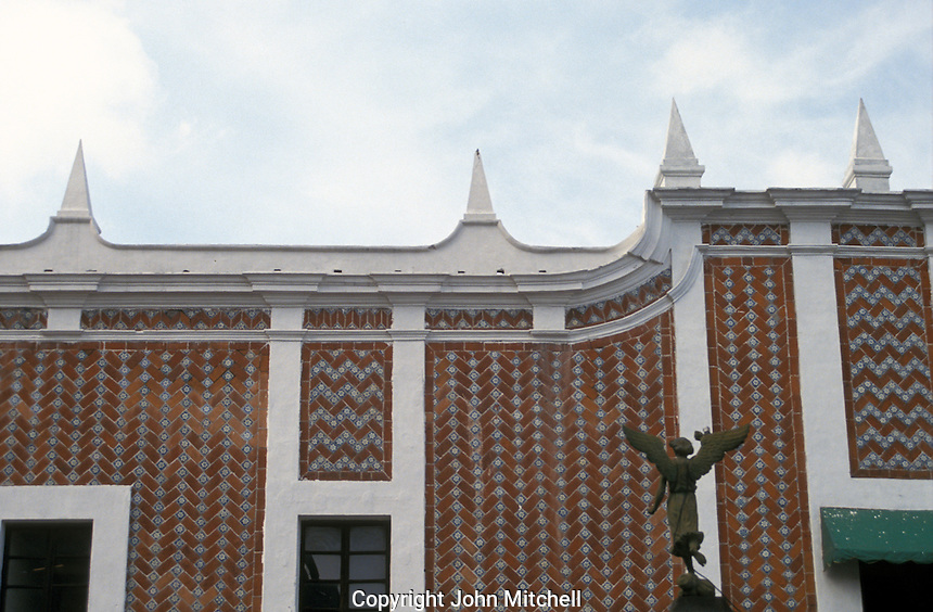 Angel statue and facade of a building covered in Talavera tiles in the city of Puebla, Mexico