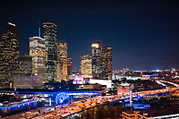 Aerial Houston Skyline  at night along IH45  in downtown area of the city.  This cityscape image show IH45 along with the Aquarium with its colorful ferris wheel plus the city hall with it rainbow of colors among the modern high rise skyscrapers.  Houston has some of the tallest buildings in the southern US and the tallest  buildings in Texas. This city has a lot to offer from it culture events,  parks, to it business friendly enviorment you can find it all here.