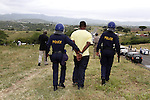 NKANDLA - 11 January 2014 - An African National Congress supporter, who is handcuffed is frog marched down to an awaiting police van after he had participated in a stone throwing incident where EFF leader Julius Malema had handed over a house to a grandmother looking after four children. Picture: Allied Picture Press/APP
