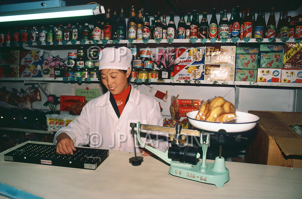 September, 1985. Shaanxi Province, China. People working in business establishments in Wuqi, suchas this general store which is run by the government.