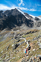 A woman trail runner walks along a group of Wallis sheep while on the Via Valais, a multi-day trail running tour connecting Verbier with Zermatt, Switzerland.