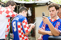 Fans of Croatia text at halftime of their match against Brazil on June 13, 2006 at the Scorpio Bar in New York City.<br /> <br /> The World Cup, held every four years in different locales, is the world's pre-eminent sports tournament in the world's most popular sport, soccer (or football, as most of the world calls it).  Qualification for the World Cup is open to any country with a national team accredited by FIFA, world soccer's governing body. The first World Cup, organized by FIFA in response to the popularity of the first Olympic Games' soccer tournaments, was held in 1930 in Uruguay and was participated in by 13 nations.    <br /> <br /> As of 2010 there are 208 such teams.  The final field of the World Cup is narrowed down to 32 national teams in the three years preceding the tournament, with each region of the world allotted a specific number of spots.  <br /> <br /> The World Cup is the most widely regularly watched event in the world, with soccer teams being a source of national pride.  In most nations, the whole country is at a standstill when their team is playing in the tournament, everyone's eyes glued to their televisions or their ears to the radio, to see if their team will prevail.  While the United States in general is a conspicuous exception to the grip of World Cup fever there is one city that is a rather large exception to that rule.  In New York City, the most diverse city in a nation of immigrants, the melting pot that is America is on full display as fans of all nations gather in all possible venues to watch their teams and celebrate where they have come from.