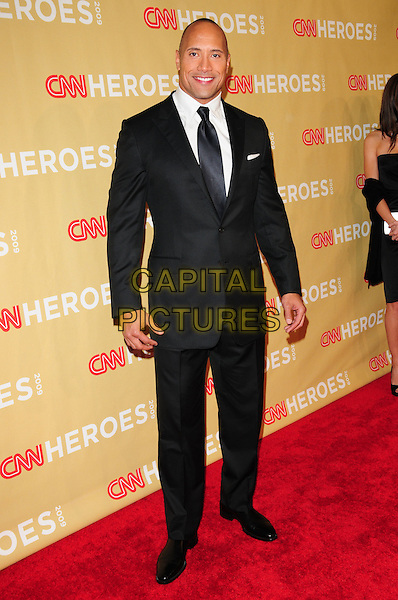 "DWAYNE ""THE ROCK"" JOHNSON.at The 3rd Annual CNN Heroes: An All-Star Tribute held at The Kodak Theatre in Hollywood, California, USA,  November 21st 2009                                                                   .full length grey gray black suit tie white shirt .CAP/RKE/DVS.©DVS/RockinExposures/Capital Pictures"