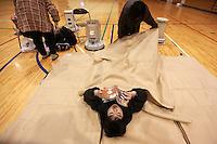 HHY24. HACHINOHE (JAPÓN), 14/3/2011.- El pequeño Rui Kumi es arropado por su madre Tomeko en un centro de evacuación en Hachinohe en la prefectura de Aomori (Japón) hoy, lunes, 14 de marzo de 2011. El centro de evacuación hospeda a más de mil vecinos que se han quedado sin nada después de que el terremoto y el posterior tsunami devastaran sus hogares el pasado 11 de marzo de 2011. Muchos residentes han regresado a sus hogares aunque todavía muchos permanecen en los centros de evacuación al no poder volver a sus hogares debido a las réplicas que desde el viernes sacuden sus casas ahora casi derruidas. EFE/How Hwee Young.