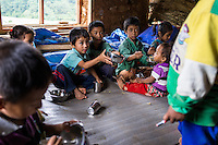 Children offer extra food to a young child during lunch time in the SOS Children's Villages Child Care Space canteen in Rayale, Nepal on 1 July 2015. The Child Care Space was set up by SOS Children's Villages soon after the earthquake so that the children of the village can come together to play, learn, and get over the trauma of the disaster as well as get regular daily meals. This also allows their parents to be free to reconstruct their homes and go off to get rations and relief kits. Photo by Suzanne Lee for SOS Children's Villages
