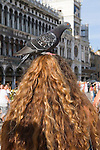 Venice Italy 2009. St Marks Square ( Piazza San Marco)  female tourist with pigeon on her head. <br /> <br /> Venice is like a crumbling open air museum and sinking under the weight of 20 million visitors a year. Only 30% of Venice's visitors stay overnight the rest stay out of town or on their cruise ships.