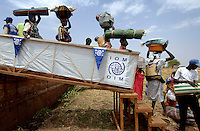 Dinka women and children carry their belongings as they disembark a barge after a two-day long journey returning displaced persons after the civil war.  They have travelled from Juba to their homeland of Bor as part of a  resettlement programme which is organised by the IOM (International Organisation for Migration).  Tens of thousands of Dinka tribespeople are among the estimated 3.8 million people displaced during the two-decade long conflict between the government and the SPLA (Sudanese People Liberation Army)...