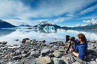 Photographer man takes photo from tripod and shore of ice berg and Colony Glacier at Inner Lake George. Summer. Southcentral, Alaska.   People/person<br /> <br /> (C) Jeff Schultz/SchultzPhoto.com