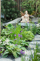 Asian Oriental statue ornament in garden with irises, primroses, pine tree, stone path walkway, in spring blooms, around a water feature