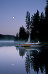 Moon at dawn over sailboat at Jenkinson Lake, Sly Park, El Dorado County, Sierra foothills, California