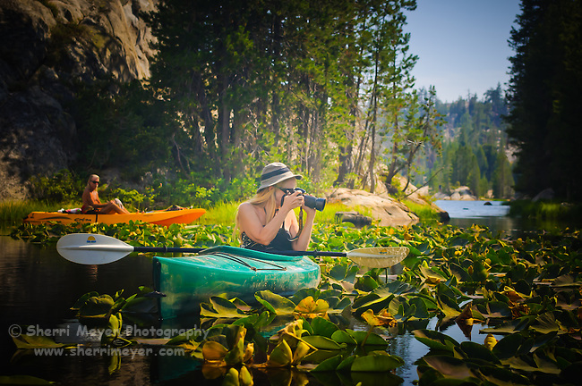 Couple kayaking through lily pads on Utica Reservoir, Alpine County, California.