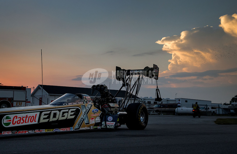 Aug. 30, 2013; Clermont, IN, USA: The car of NHRA top fuel dragster driver Brittany Force is towed back to the pits as the sun sets during qualifying for the US Nationals at Lucas Oil Raceway. Mandatory Credit: Mark J. Rebilas-