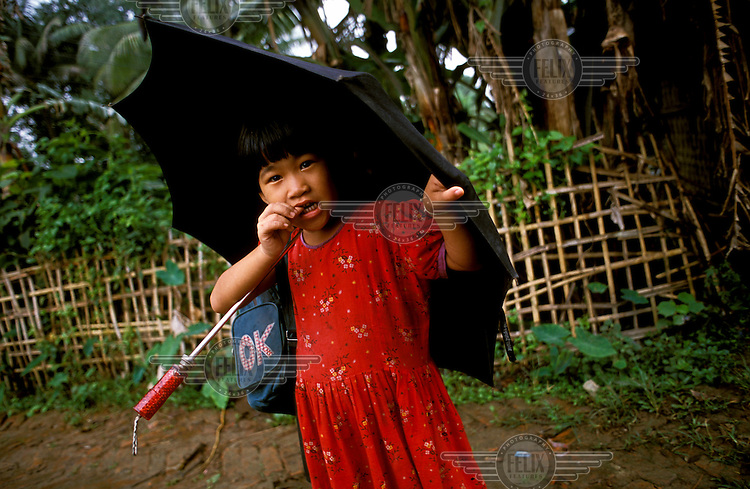 A Chakma (Changma) girl shelters under an umbrella on her way to school.