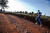 A foreign man training with Kenyan runners in Iten, Kenya.