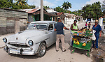 Finca La Vigia, San Francisco de Paula, Cuba; a street vendor sells fruits and vegetables from a cart to a customer in a classic car, outside the entrance to the Hemingway Museum