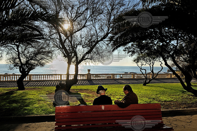 An old couple sit on a park bench with a view of the Atlantic Ocean.